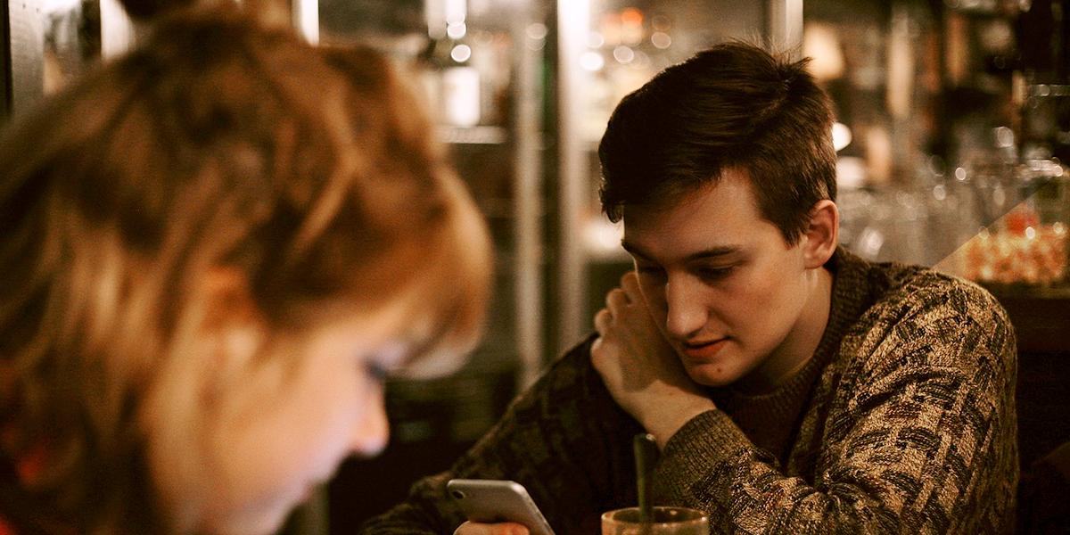 Chica y chico mirando sus móviles